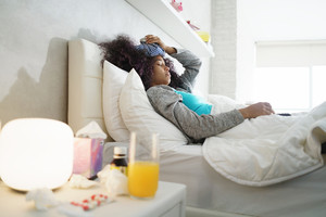 Sick african american girl with flu at home, ill young black woman with fever and ice bag on head, resting in bed.