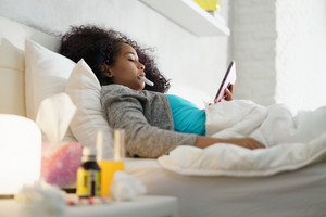 Sick african american girl with flu lying in bed at home. Ill young black woman with cold checking temperature with thermometer and watching movie on tablet.