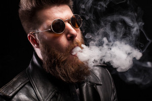 Side portrait of sexy bearded man in leather jacket with sunglasses over black background. Studio lighting. Dramatic portrait.