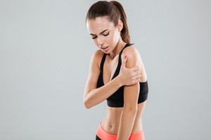 Side view of a fitness woman with pain in her shoulder over gray background