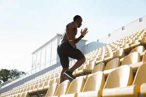 Side view of a sporty young man runner on a stadium running upstairs