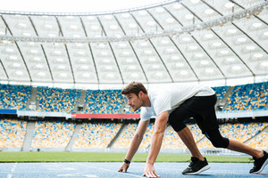 Side view of a young athlete at starting position ready to start a race at the stadium