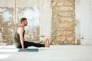 Side view of a young man doing yoga exercises indoors