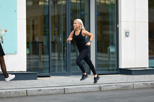 Side view of sporty woman running fast in minimalist urban environment