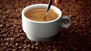 side view of white cup of black coffe on coffee beans. Coffee cream moving in cup
