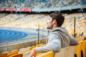 Side view of young man in sportswear with earphones sitting on a stadium seats