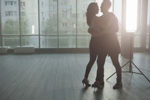 Silhouette of beautiful couple dancing and enjoying the music. Passionate moment. Skillful dancers.