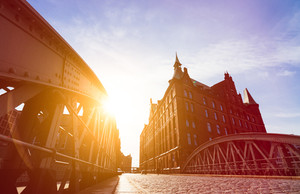 Silhouette of Bridge and Buildings in evening sun rays in low angle view. Speicherstadt Hamburg. Famous landmark of old buildings made with red bricks