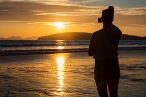 Silhouette Woman Photographing Sunset At Beach