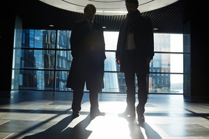 Silhouettes of two businesspeople partly illuminated with last beams of setting sun coming from panoramic window of office lobby
