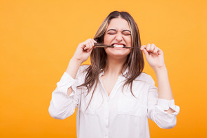 Silly young girl in white shirt biting her hair over yellow background.