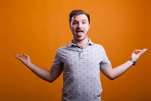 Silly young man showing his tongue to the public over an yellow orange background in studio photo