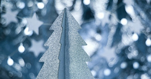 Silvery cardboard Cristmas tree close up with sparkling stars and lens flare in cold tones loop