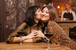 Sisters celebrating their friendship gossiping over a glass of wine in a vintage pub. Girl kissing her friend cheek