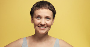 sleepy 30s woman with a short haircut on a yellow morning atmosphere background