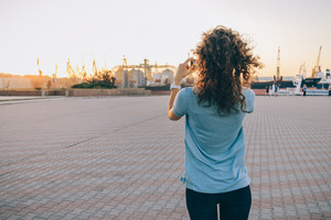 Slim girl with curly hair takes pictures of city landscape at sunset