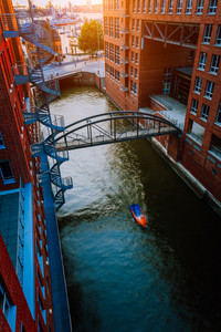 Small Boat under bridge over canal between red brick buildings in the old warehouse district Speicherstadt in Hamburg in golden hour sunset light, Germany. View from above