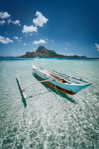 Small fishing banca boat in front of Cadlao Island in crystal clear shallow water, low tide, amazing nature of Palawan, Philippines