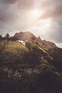 Small house nestled into the steep rock overgrown with palms and sugarcane. Sun Rays coming through the clouds. on Santo Antao, Cape Verde
