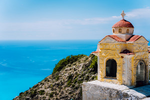 Small orange colored Hellenic shrine Proskinitari on the cliff edge with defocused sea view in the background