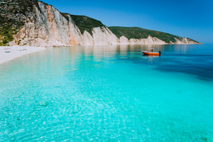Small red boat on clear blue sea water near to amazing beach on mediterranean island. Summer beach vacation relaxation concept