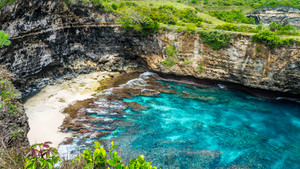Small Sandy Beach in front iof Stone arch over the sea. Broken beach. Rock coastline. Nusa Penida, Indonesia