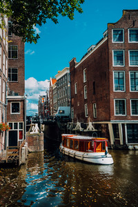 Small Tourist boat floating picturesque dutch channel passing traditional brick houses. Colorful cityscape in Amsterdam Netherlands, Europe. City trip concept