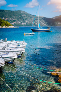 Small tourist boats for rent docked on the shore. Turquoise bay, crystal clear water. Amazing summer vacation on mediterranean island.