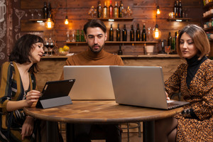 Smart man in casual style working on his laptop between two female colleagues in a coffee shop.