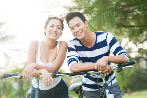Smiling Asian couple with bicycles looking at the camera