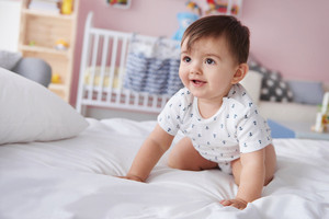 Smiling baby boy crawling on the bed