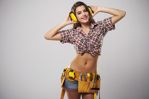 Smiling beautiful female construction worker with ear protectors