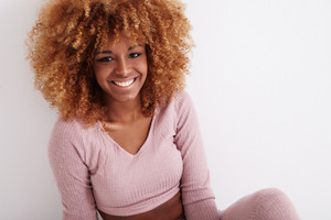 smiling black woman with blonde shinig curly hair
