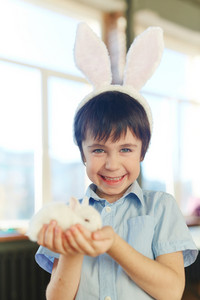 Smiling boy with white rabbit looking at camera