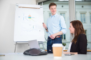 Smiling Businessman Giving Presentation To Colleague In Office