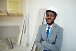 Smiling businessman in hardhat looking at camera