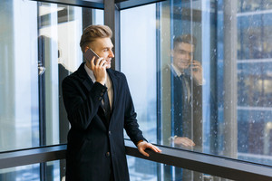 Smiling businessman speaking on mobile phone with client