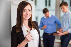 Smiling Businesswoman Holding Coffee Mug With Colleagues Discuss