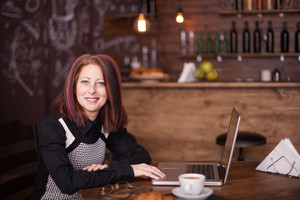 Smiling businesswoman with a laptop in font of her sitting and enjoying a coffee in vintage coffee shop or restaurant
