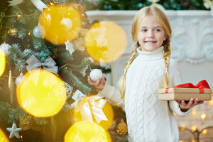 Smiling child holding packed xmas gift while standing by decorated firtree