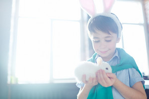 Smiling child looking at cute white fluffy bunny in his hands