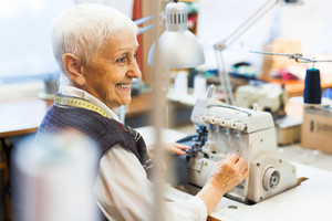 Smiling clothier working by sewing machine