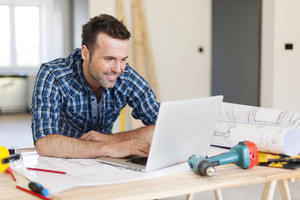 Smiling construction worker working with laptop