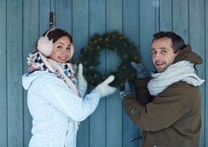 Smiling couple holding coniferous wreath against wooden door
