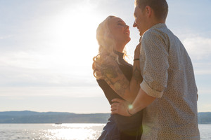 Smiling couple in romantic embrace on beach at summer