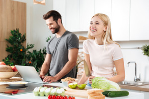 Smiling couple using notebook to cook in their kitchen and laughing