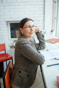 Smiling elegant-looking senior woman wearing eyeglasses sitting in profile and looking out window, waist-up portrait