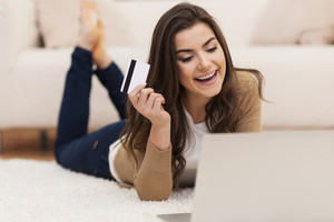 Smiling female paying for shopping by credit card