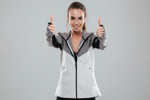 Smiling female runner in warm clothes showing thumbs up and looking at the camera over gray background