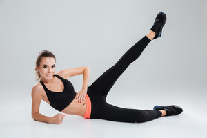 Smiling fitness woman lying and warming up on the floor in studio